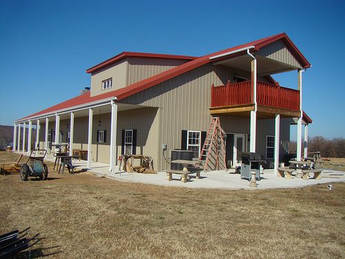 Two story barndominium with awning and red metal roof
